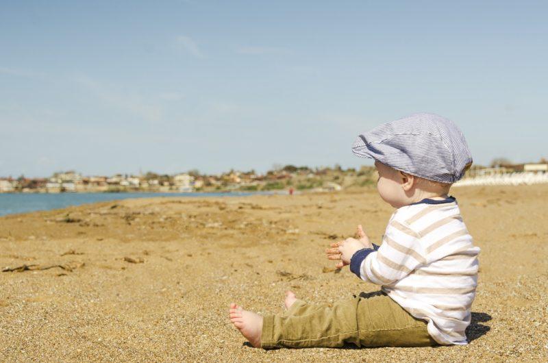 Bebe con Ropa mi Corazon es suyo sentado en la playa